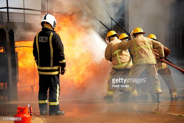 firemen training, firemen spraying water at fire at training facility, rear view - international firefighters day stock pictures, royalty-free photos & images