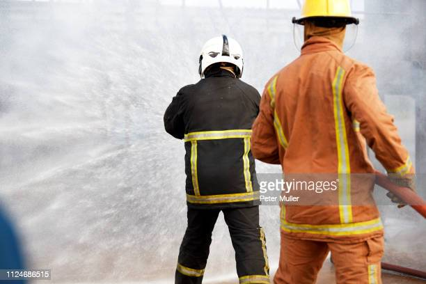 firemen training, firemen spraying water at training facility, rear view - international firefighters day stock pictures, royalty-free photos & images