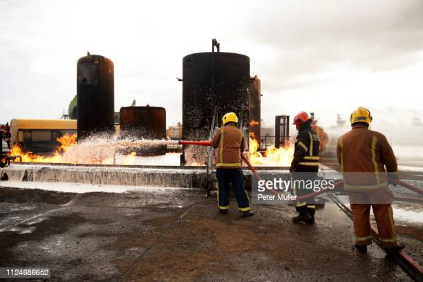 firemen training, spraying firefighting foam onto oil storage tank fire at training facility - international firefighters day stock pictures, royalty-free photos & images