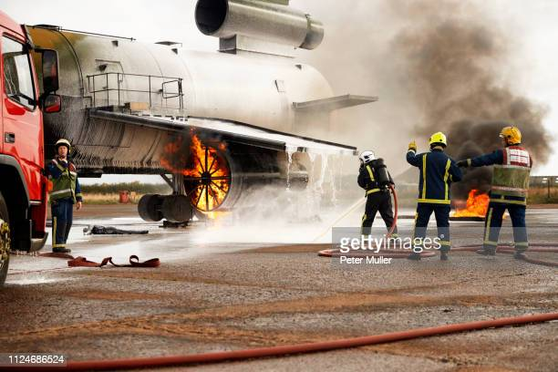 firemen training, spraying water at mock airplane engine - international firefighters day stock pictures, royalty-free photos & images