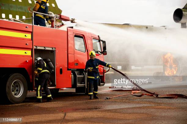 firemen training, spraying water from fire engine at mock airplane engine - international firefighters day stock pictures, royalty-free photos & images