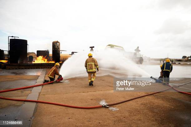 firemen training, spraying water onto fire at training facility - international firefighters day stock pictures, royalty-free photos & images