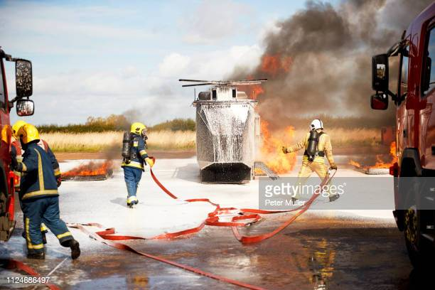 firemen training, team of firemen extinguishing mock helicopter fire at training facility - international firefighters day stock pictures, royalty-free photos & images