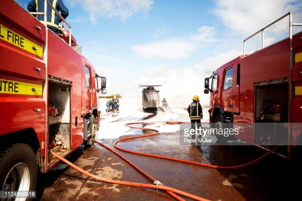 firemen training, team of firemen spraying firefighting foam at mock helicopter at training facility - international firefighters day stock pictures, royalty-free photos & images