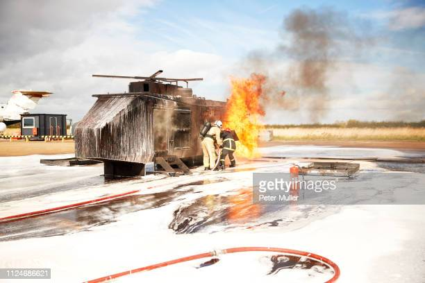 firemen training, team of firemen spraying firefighting foam at mock helicopter fire at training facility - international firefighters day stock pictures, royalty-free photos & images