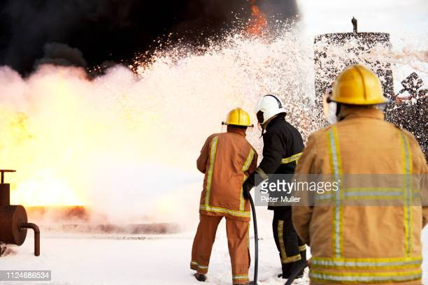 firemen training, team of firemen spraying firefighting foam on fire at training facility, rear view - international firefighters day stock pictures, royalty-free photos & images