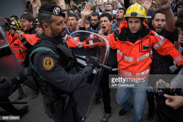 Firemen try to hold a group of people in front of Spanish Guardia Civil officers outside a polling station in San Julia de Ramis on October 1 on the...