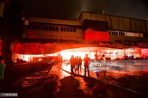 Firemen try to put out a fire inside a mall following a 6.4-magnitude quake in General Santos City, in southern island of Mindanao, on October 16,...