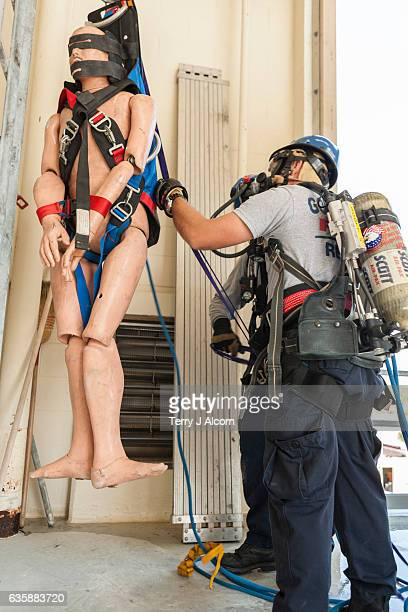 firemen use ropes to begin hoisting dummy to second story - hoisting stock pictures, royalty-free photos & images