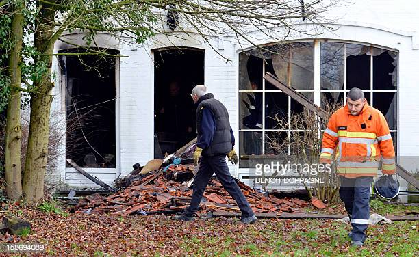 Firemen walk at the scene of a house fire in Hanzinne Florennes on December 24 2012 after a blaze brokeout around 4am killing a woman and her child...
