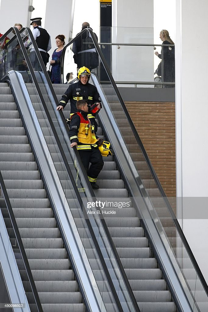 Firemen walk down an escalator as people evacuate The Shard on June 5, 2014 in London, England. The Shard, London's tallest building standing at 310 meters high, was surrounded by fire brigade who evacuated 900 people after smoke was reported in the basement.