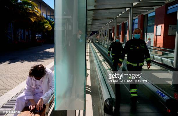 Firemen walk next to a health worker outside the Ifema convention and exhibition centre in Madrid on April 03 2020 where a temporary hospital for...