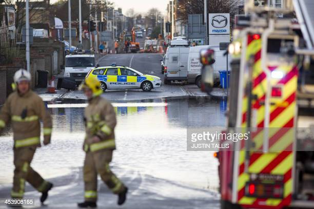 Firemen walk past a flooded street in Lowestoft in the east of England on December 6 2013 after a tidal surge hit locations along the east coast of...