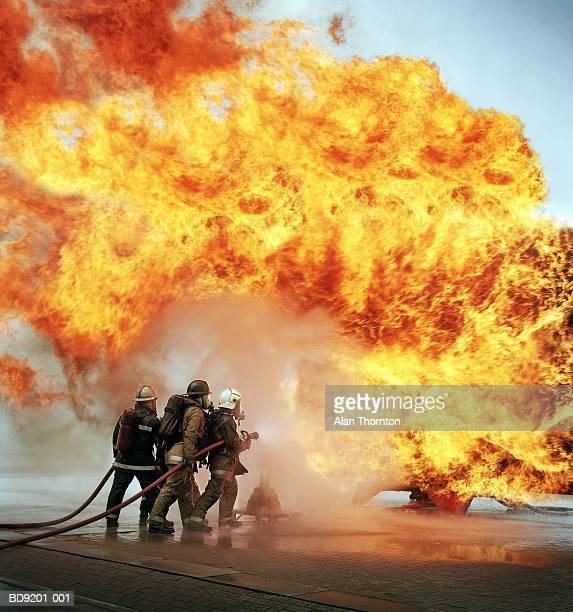 firemen with hose fighting firewall - 消防士 ストックフォトと画像