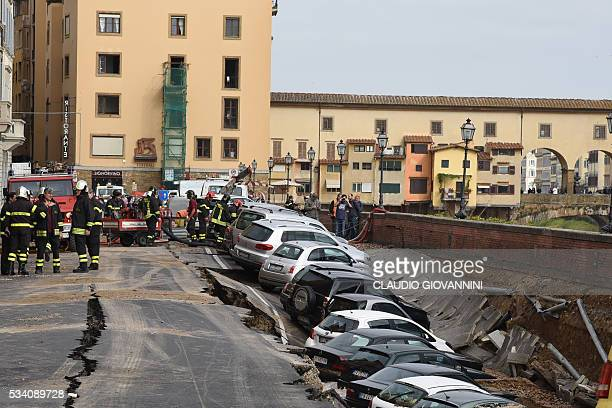 TOPSHOT Firemen work along the Arno river where a collapsing of two hundred meters by seven wide occured early on May 25 2016 on Lungarno Torrigiani...