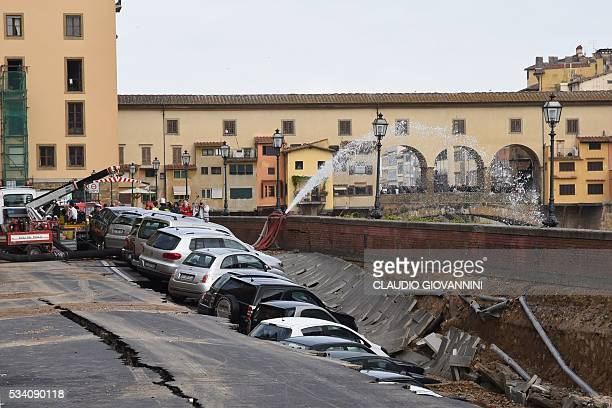 Firemen work along the Arno river where a collapsing of two hundred meters by seven wide occured early on May 25 2016 on Lungarno Torrigiani in...