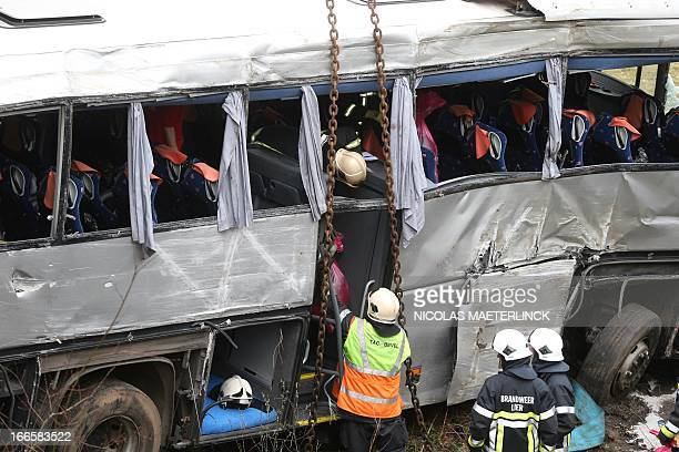 Firemen work on a bus near the wreckage after it crashed off the E34 highway near Ranst Antwerp province on April 14 2013 At least five people died...