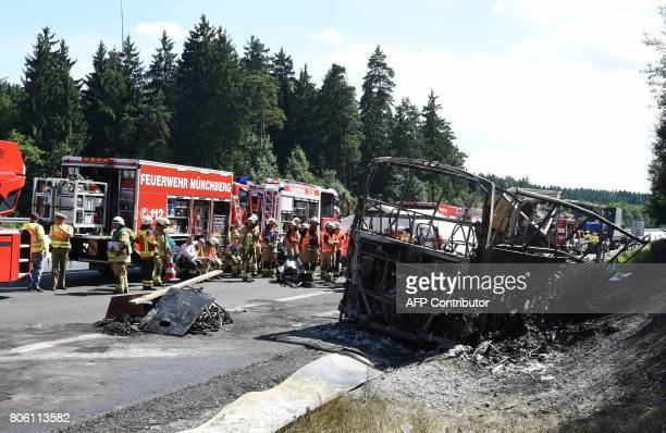 Firemen work on the site of a bus crash on the A9 highway near Muenchberg, southern Germany, on July 3, 2017. Up to 18 people were feared dead after...