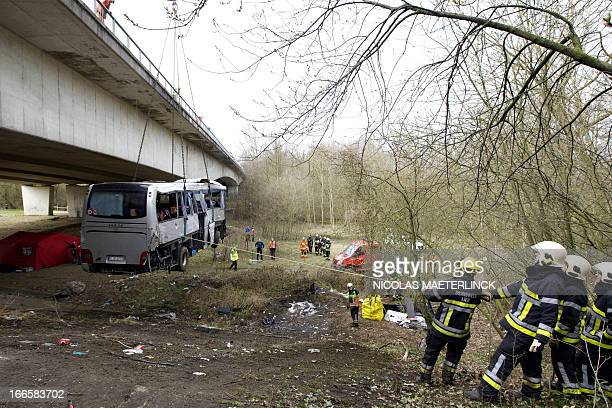 Firemen work to hoist up a bus after a crash off the E34 highway near Ranst Antwerp province on April 14 2013 At least five people died and several...