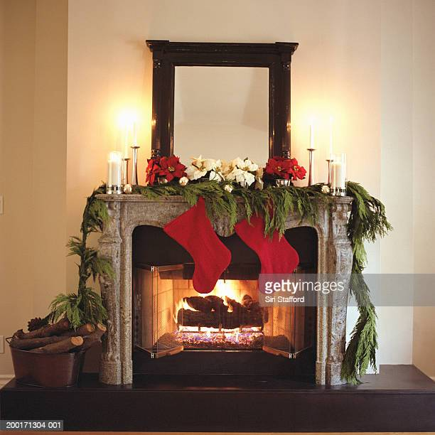 Fireplace decorated with Christmas stockings and Poinsettias