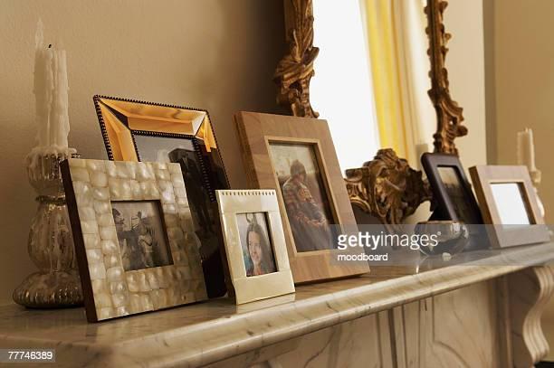 fireplace mantel with framed pictures - consolo de lareira - fotografias e filmes do acervo