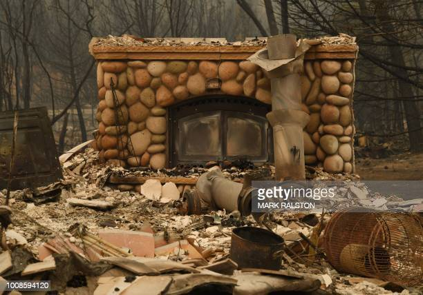A fireplace still stands amongst a burnt house in the Keswick neighborhood of Redding as the Carr fire continues to spreads towards the town of...