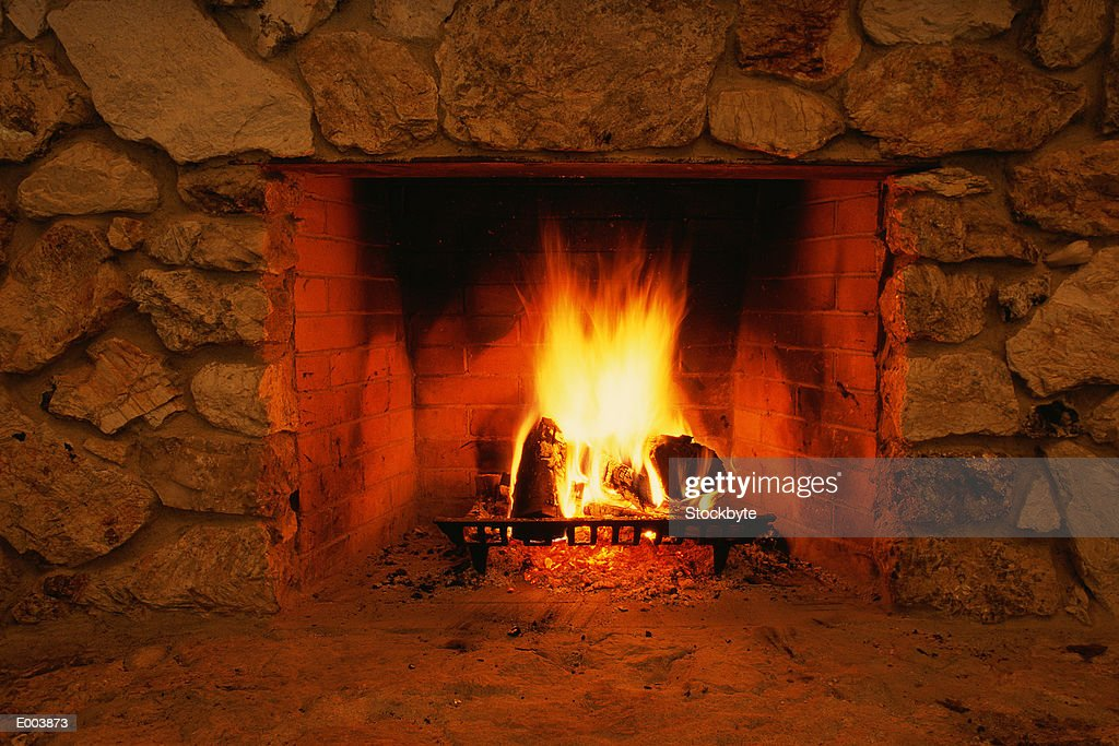 Fireplace with roaring fire : Stock Photo