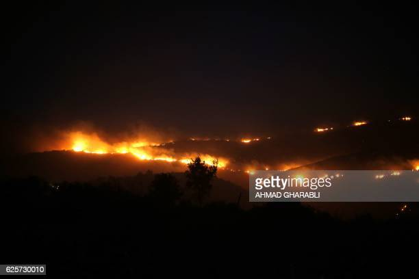 TOPSHOT Fires burn in the horizon as firefighters battle to control a fire that broke out in the Israeli town of Nataf west of the Arab Israeli town...