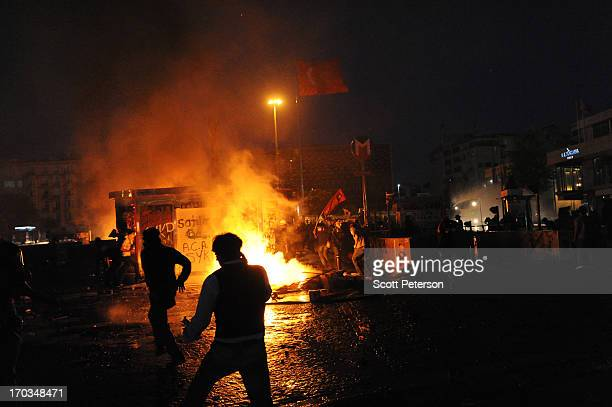 Fires rage as Turkish police battle anti-government protestors to reestablish police control of Taksim Square after an absence of 10 days on June 11,...