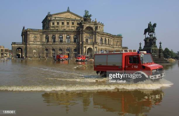 A firetruck drives through floodwaters in front of the Semper Opera House August 17 2002 in Dresden Germany Firefighters are pumping water out of the...