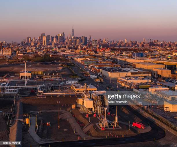 firetruck is on duty near a power plant in the industrial zone in east williamsburg, brooklyn, new york, with the remote view of downtown manhattan in the backdrop. - brooklyn new york stock pictures, royalty-free photos & images