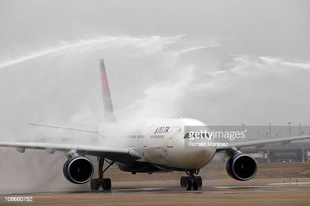 Firetrucks spray water as the Green Bay Packers arrive on a Delta charter plane at Dallas Fort Worth International Airport on January 31 2011 in...