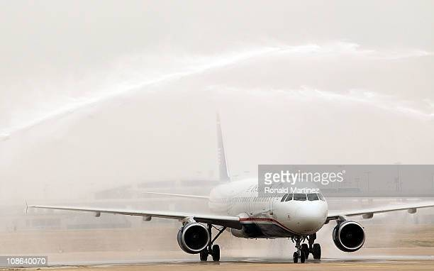 Firetrucks spray water as the Pittsburgh Steelers arrive on a US Airways charter plane at Dallas Fort Worth International Airport on January 31 2011...