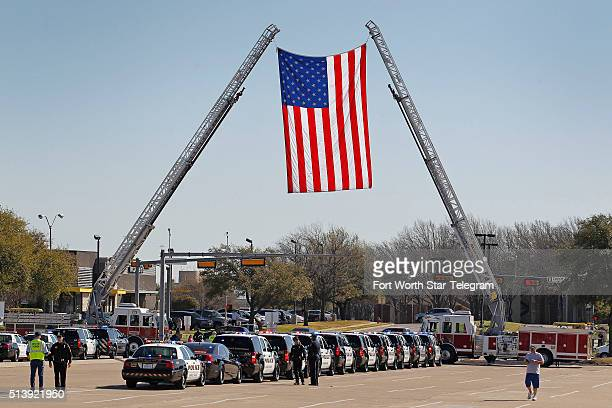 Firetrucks support a huge US flag over the east entrance of Pennington Field in Fort Worth Texas to a memorial service for Euless Texas police...