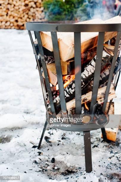 Firewood burning in metal basket
