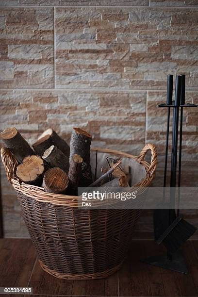 Firewood in a basket next to a hearth set