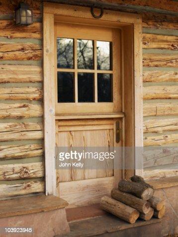 Firewood In Front Of Door Of Log Cabin Stock Photo - Getty ...