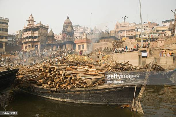 firewoods on a boat in the river, ganges river, manikarnika ghat, varanasi, uttar pradesh, india - manikarnika ghat stock pictures, royalty-free photos & images