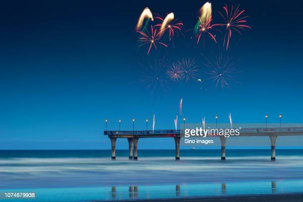 firework display above pier in sea at night, new zealand - image stock pictures, royalty-free photos & images