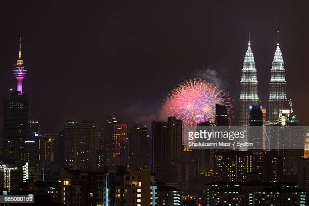 Firework Display By Illuminated Petronas Towers Amidst Buildings In City