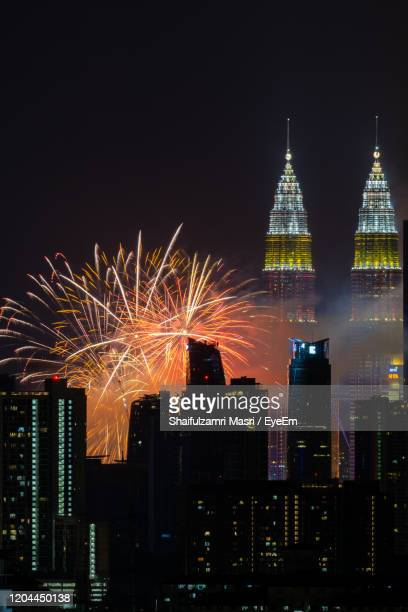firework display over city lit up at night - shaifulzamri stock pictures, royalty-free photos & images