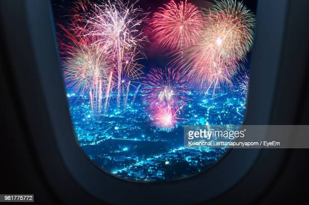 Firework Display Over City Seen Through Airplane Window At Night