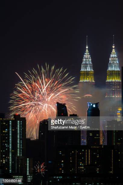 firework display over illuminated buildings against sky at night - shaifulzamri foto e immagini stock