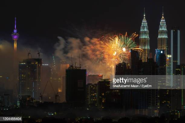 firework display over illuminated buildings in city at night - shaifulzamri eyeem stock pictures, royalty-free photos & images