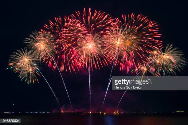 firework display over lake at night - firework display stock pictures, royalty-free photos & images