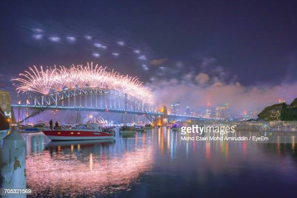 Firework Display Over River Against Sky
