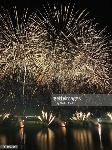 firework display over river at night - swift river stock photos and pictures