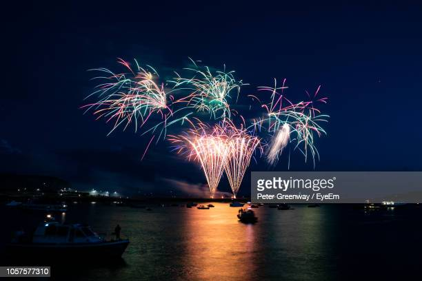 firework display over sea at night - plymouth stock photos and pictures