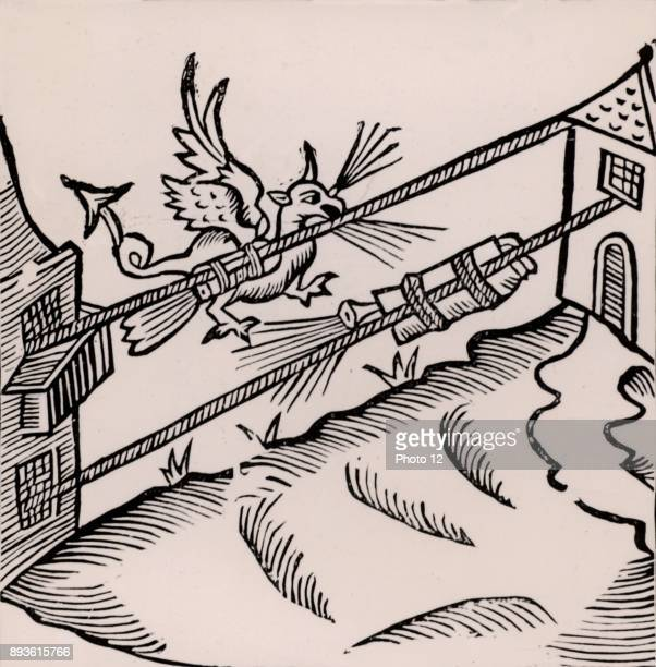 A Firework display The figure of a dragon breathing fire is attached to a rocket tied to a rope stretched between two buildings Woodcut from...