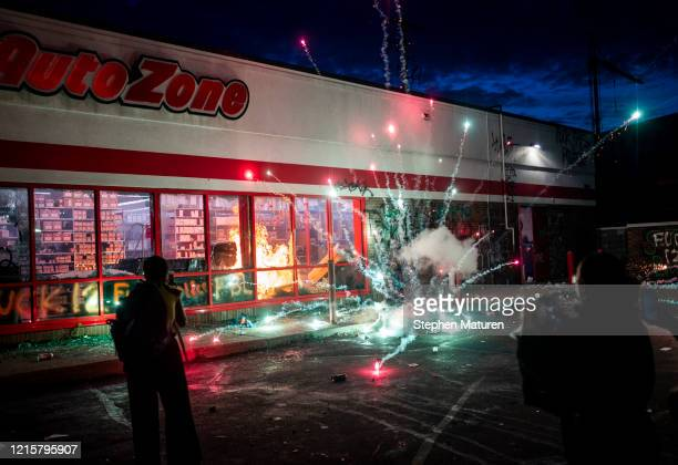 A firework explodes as a fire burns inside of an Auto Zone store near the 3rd Police Precinct on May 27 2020 in Minneapolis Minnesota Businesses near...